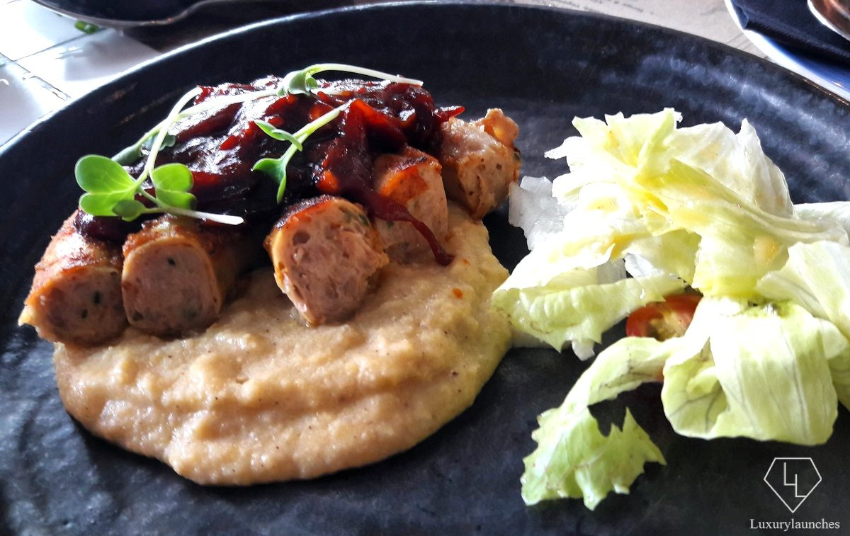 South African Pork Borewors with Chakalaka Sauce and Mealiepap with a side of Mesclun Lettuce