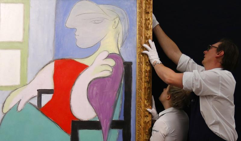 "Sotheby's employees straighten ""Femme assise pres d'une fenetre"" from 1932 by Pablo Picasso at Sotheby's in London"