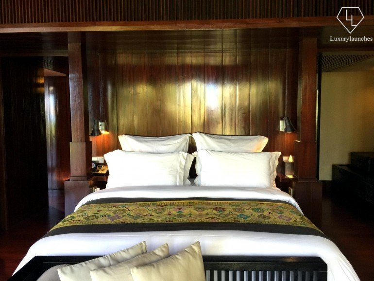 The master bedroom is furnished in dark bangkiray hardwood and woven fabrics — like the green bedspread pictured here