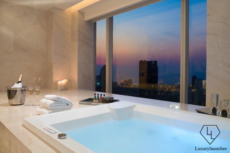 The en-suite spa bathroom featuring a Jacuzzi that overlooks the city's romantic skyline.