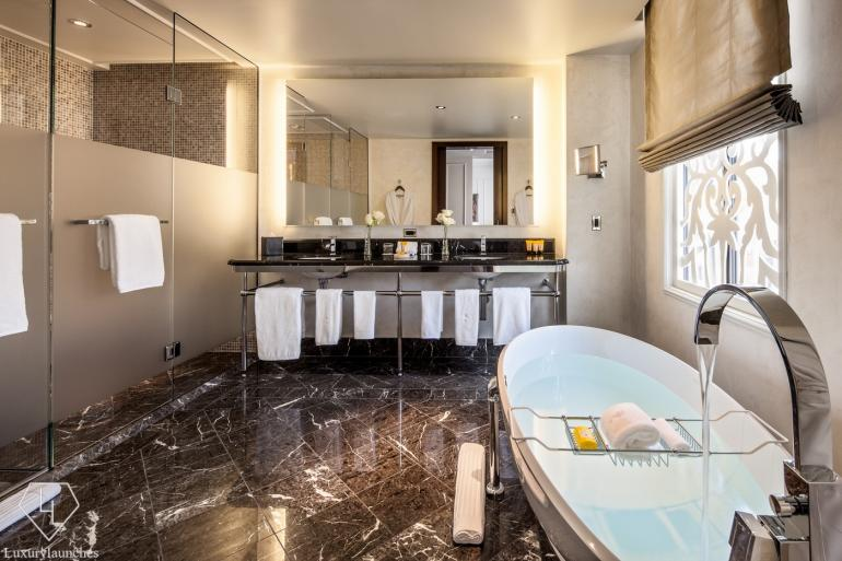 The expansive and luxurious bathroom done up in marble and tones of black and gold will make you never want to leave.
