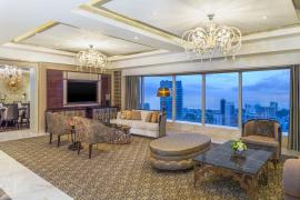 The living room luxuriously studded with handcrafted rugs and furnishings in warm gold and beige colors.