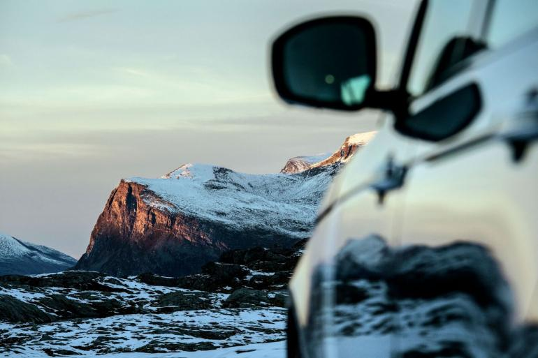 This shot was captured after driving in the early October snow on the mountain plateau beneath the Dalsnibba peak in Møre og Romsdal county. The first snow had come the weekend before we arrived in the region, and covered a gravel track that we were following. Light and timing is everything in what I do - when the things I'm photographing are so still the light becomes even more important – and this photograph was taken just as the last rays of the evening sun hit the higher mountain peaks.