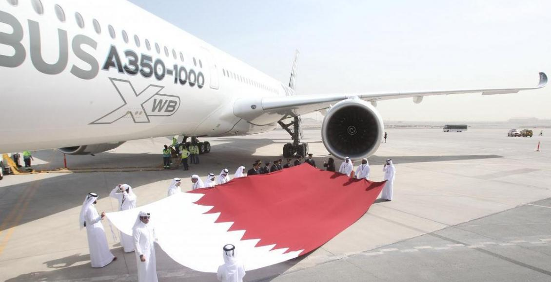 Qatar Airways staff hold the national flag next to an Airbus A350-1000 in Doha