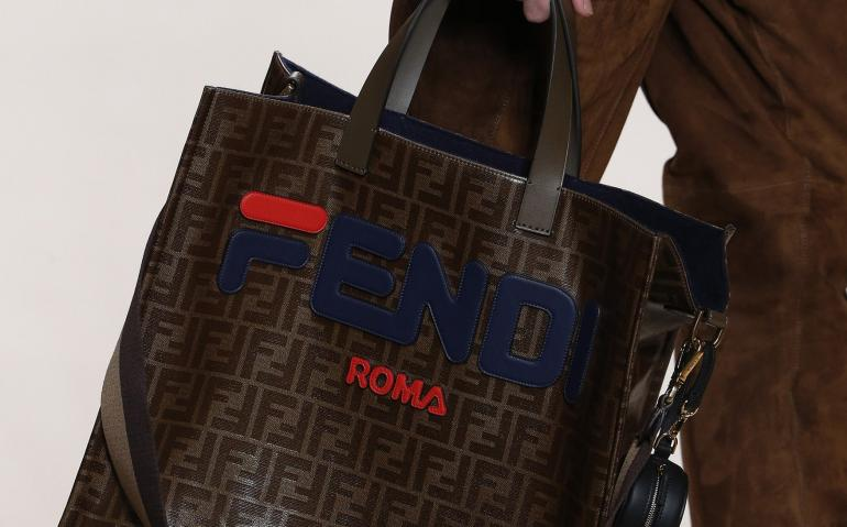 "5f1b0f42ed Items like bags and t-shirts featuring FILA's iconic ""F"" fused with the FENDI  Roma logo."